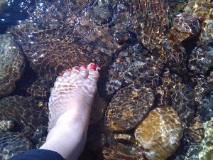Foot with red nail polish stepping into stream